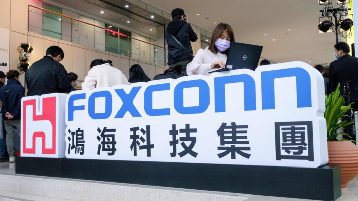 January 4, 2021, Taipei, Taiwan: A woman wearing a face mask seen working on her computer on top of Foxconn s logo duri