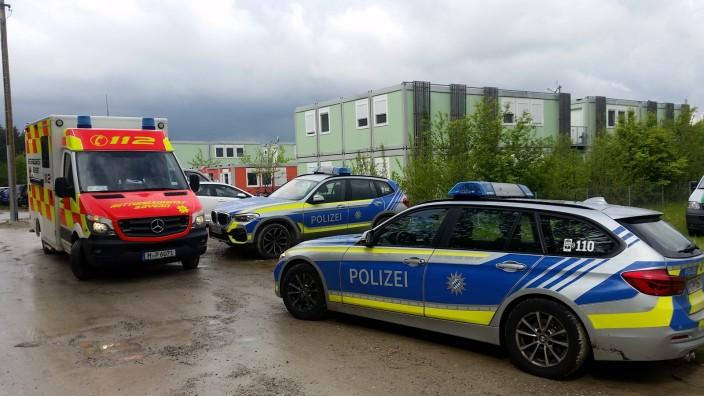 Asylunterkunft in Krailling: Vor der Flüchtlingsunterkunft stehen Polizeiwagen mit laufendem Motor, während drinnen Beamte mit einem jungen Mann verhandeln.
