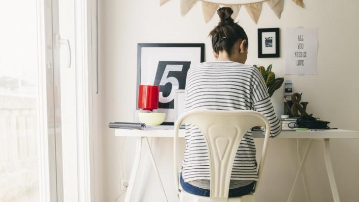 Eine Frau sitzt im Homeoffice am Schreibtisch