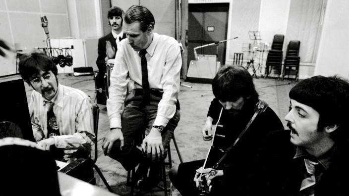 Publicity photo of the Beatles John Lennon Ringo Starr George Martin George Harrison Paul McCar