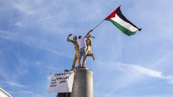 Deutschland, Berlin, Neukölln am 09.05.2021: Zwei Männer auf dem Hermannplatz Statue mit der Palästina Fahne / Flagge u