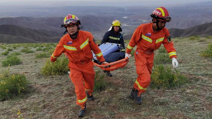 Nach Unwetter: Rettungskräfte auf der Suche nach Läufern beim Tragen ihrer Ausrüstung