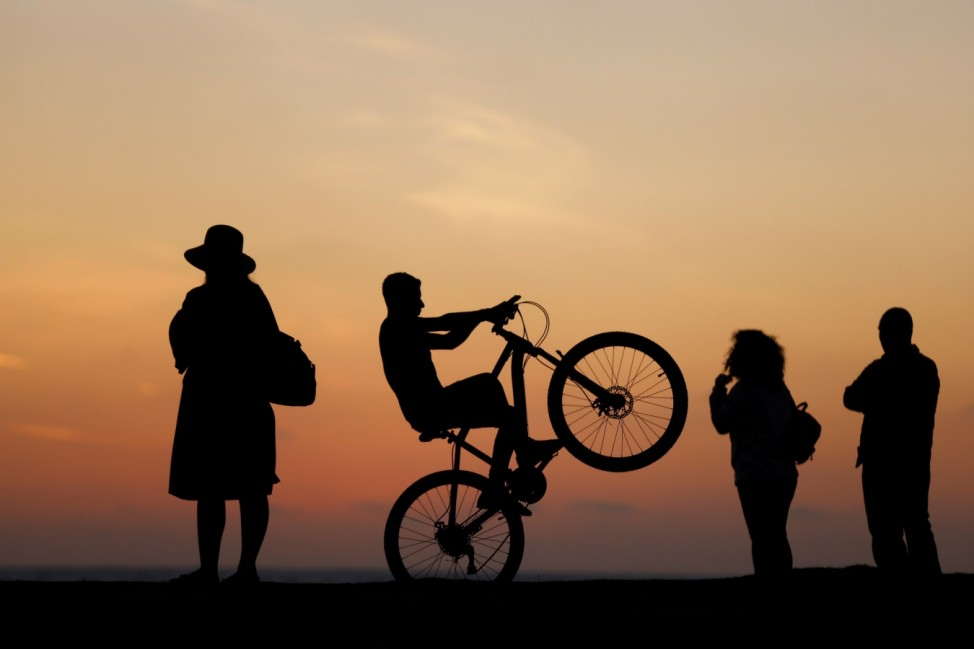 People are silhouetted as they visit on a promenade during sunset at a beach as the Israel-Hamas ceasefire holds, in Ashkelon