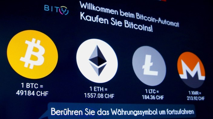 FILE PHOTO: The exchange rates and logos of Bitcoin, Ether, Litecoin and Monero are seen on the display of a cryptocurrency ATM in Zurich