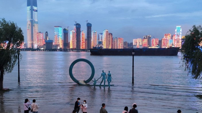 People stand next to overflowing section of Yangtze River following heavy rainfall, in Wuhan
