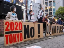 May 17, 2021, Tokyo, Japan: Protesters wearing masks hold signs in a line to form the words 2020 No! Olympics during an