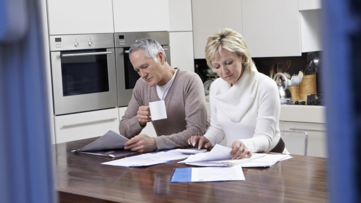 Middle-aged couple reading documents in kitchen,model released, Symbolfoto,property released PUBLICATIONxINxGERxSUIxAUTx