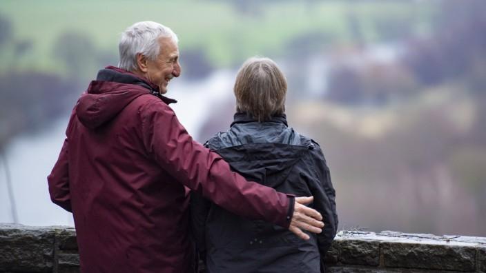 Feature Altersversorgung Ein Mann und eine Frau stehen auf einer Aussichtsplattform und schauen auf einen Fluss und eine