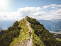 Drone shot of woman hiking on mountain towards peak against sky model released Symbolfoto PSIF00420