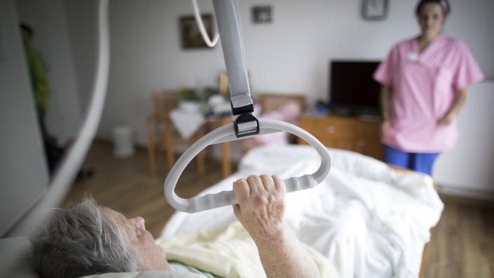 Eine Bewohnerin in einem Altenpflegeheim haelt sich an einem Haltegriff fest. 04.08.2017, Eberswalde-Finow. Eberswalde-