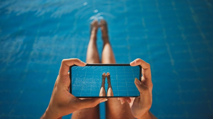 From above of crop anonymous barefoot female taking photo of legs on cellphone over swimming pool with pure water, Model