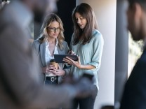 Businesswomen working over digital tablet while standing with colleague in background at office model released Symbolfot