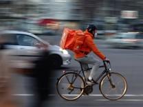 03.03.2021, Berlin, GER - Mitarbeiter von Lieferando faehrt eine Bestellung mit dem Fahrrad aus. (Alltag, ausliefern, au