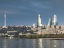 Azerbaijan, Baku, city skyline with Baku Television Tower and Flame Towers form Baku Bay, dawn. (Walter Bibikow)