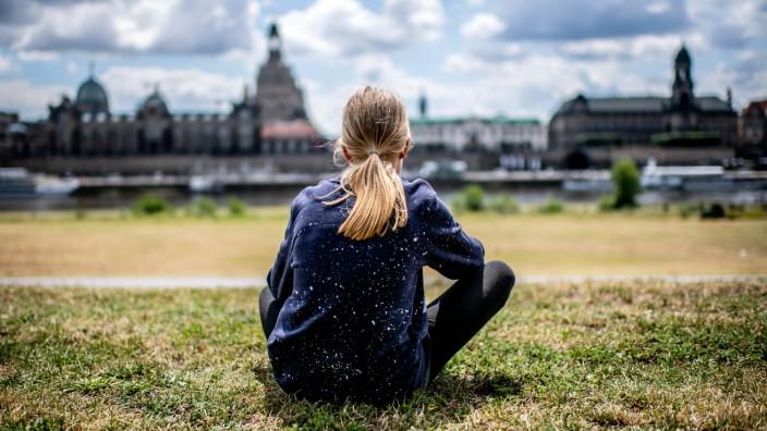16. Juli 2020: Dresden (Sachsen), Ufer an der Elbe: (Model release) Ein Maedchen sitzt am Elbufer und schaut in die Fern