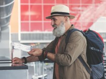 Side view beaming unshaven retire traveller giving ticket to booking office (YakobchukOlena)