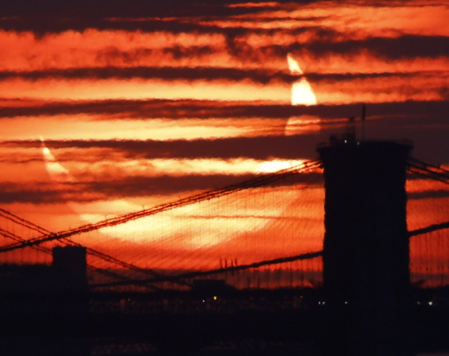 A partial solar eclipse rises behind the Brooklyn Bridge and other east river crossings in Manhattan from Bayonne, New J