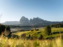 Heustadel und Hütten auf nebligen Wiesen, hinten Langkofel und Plattkofel, Seiser Alm, Südtirol, Italien, Europa *** Hay