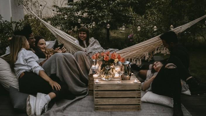 Smiling friends enjoying at social gathering in yard during sunset Sweden, Stockholm, model released, property released