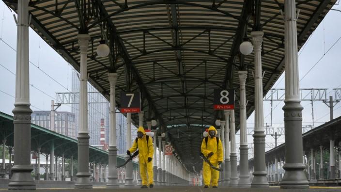 Corona in Moskau: Verfrühte Sommerferien: Arbeiter des Zivilschutzes desinfizieren einen menschenleeren Bahnsteig in einem der großen Bahnhöfe Moskaus.