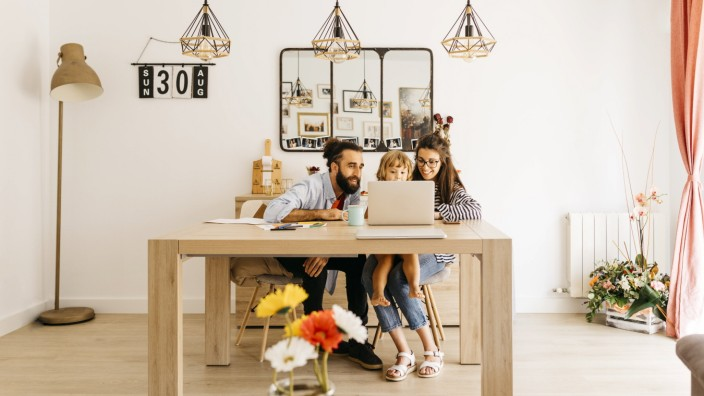 Parents with daughter using laptop on dining table at home model released Symbolfoto property released JRFF04595