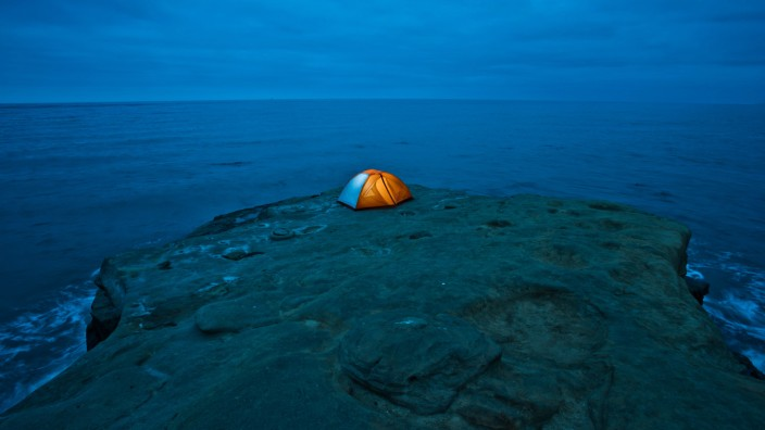 An illuminated tent sits on cliff overlooking the Pacific Ocean in San Diego CA San Diego Califor