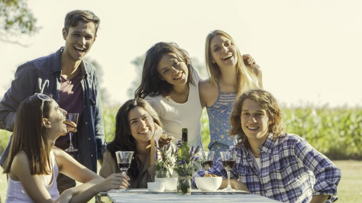 Friends posing for photo during outdoor meal together PUBLICATIONxINxGERxSUIxAUTxONLY Copyright Sig