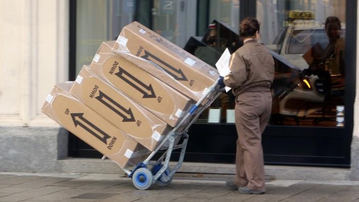Paketzustellerin von UPS United Parcels Service bei der Zustellung von Paketn in der Innenstadt München, Bayern, Deutsc