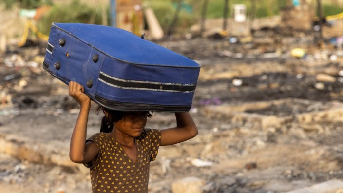 ARohingyarefugee carries her belongings to a temporary shelterafter afiredestroyed a Rohingya refugee camp on Saturday night, in New Delhi