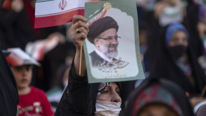 Iran Goes to the Polls in Presidential Election A female supporter of the Iranian president elect Ebrahim Raisi holds-up