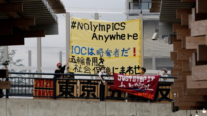 Anti-Olympics group's members display banners as they stage a rally next to the village plaza of the Tokyo 2020  Olympic and Paralympic Village while media take part in a press tour inside the facility in Tokyo