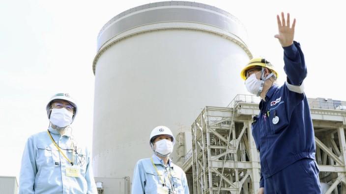 Mihama nuclear power plant in Japan File photo taken April 24, 2021, shows Fukui Gov. Tatsuji Sugimoto (L) visiting the