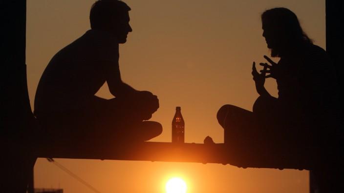 Sommerabend in München junge Leute sitzen auf dem Geländer der Hackerbrücke und genießen den Sonnen