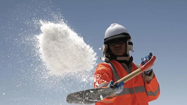 A worker throws salt at Uyuni salt lake