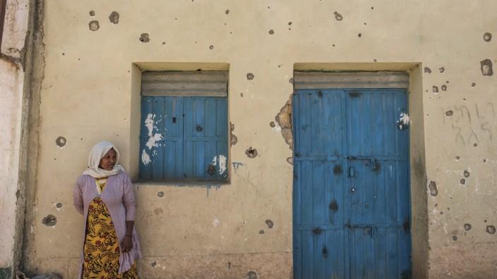 In Tigray leidet vor allem die Zivilbevölkerung unter dem Krieg - wie diese Frau, die an einem von Kugeln getroffenen Haus steht.