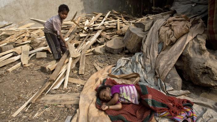 """Neue Bücher zur Geschichte der Sklaverei: Rund 40 Millionen Menschen leben heute in """"moderner Sklaverei"""", mehrheitlich Kinder und Frauen: Vierjähriger mit schlafender anderthalbjähriger Schwester bei der Arbeit in einem Feuerholzhandel in Guwahati, Indien"""