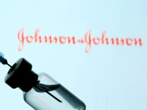 FILE PHOTO: Vial and syringe are seen in front of displayed Johnson & Johnson logo in this illustration taken
