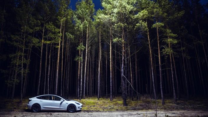 Ein Tesla Model 3, beleuchtet von einer Drohne, steht auf einem Waldweg nahe Grünheide. Grünheide, 19.01.2020 *** A Tesl