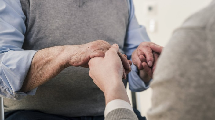 Close up of senior man and young man holding hands model released Symbolfoto property released PUBL