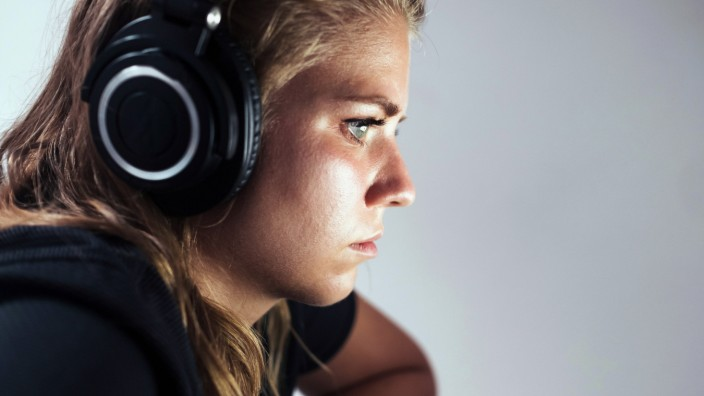 Focused young female freelancer in casual wear with wireless headphones sitting on sofa and using laptop while working o