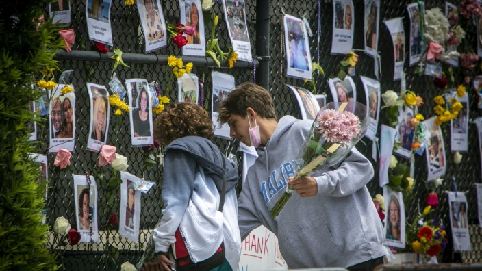 Miami: Zwei Jungen hinterlassen Blumen an einer provisorischen Gedenkwand für Opfer und Vermisste des Hochhaus-Unglücks in Miami