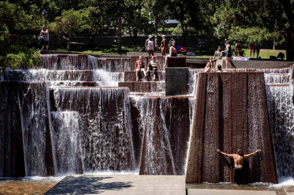 People cool off in a public fountain during hot weather in Portland