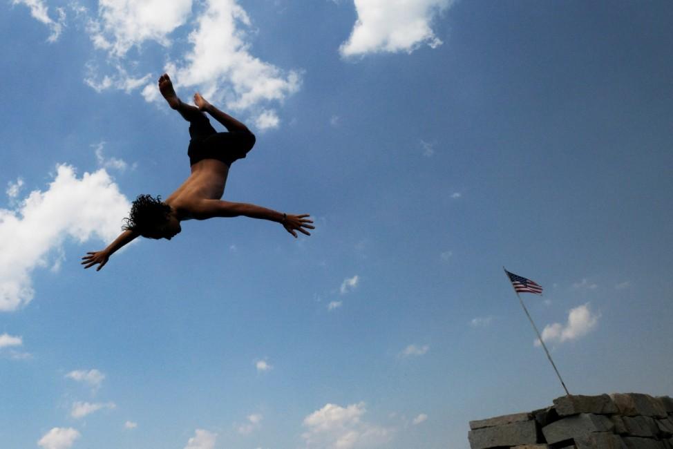 Kids jump off a breakwater into the ocean in Gloucester