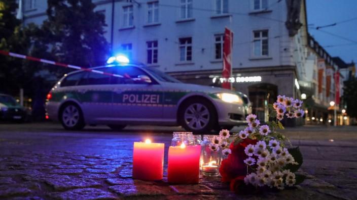 Messerangriff in Würzburg: Menschen legen Blumen und Kerzen am Tatort nieder.