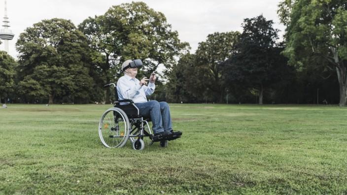 Senior man sitting in wheelchairin a park using Virtual Reality Glasses model released Symbolfoto PUBLICATIONxINxGERxSUI