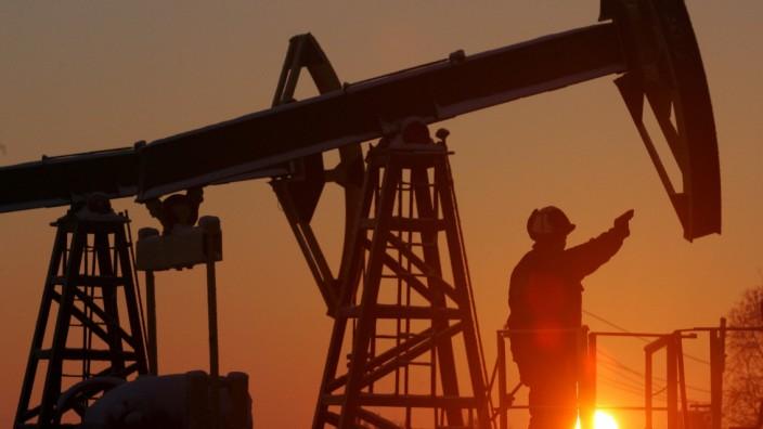 Worker stands under a derrick at Yuganskneftegaz oil processing facility at Mamontovskoye oilfield outside the Siberian town of Nefteyugansk