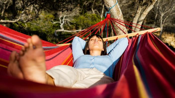young woman caucasian sleeping in hammock Sant Elm, IB, Spain PUBLICATIONxINxGERxSUIxAUTxONLY CR_PESU210416-706701-01 ,