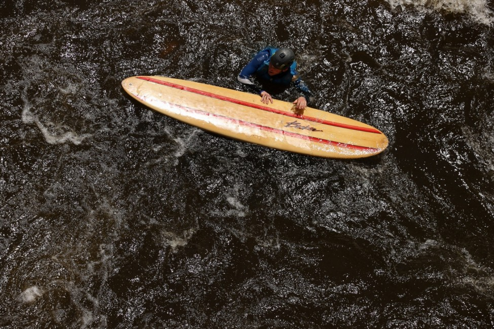 A surfer floats down the Poudre River while riding at the Poudre River Whitewater Park in Fort Collins