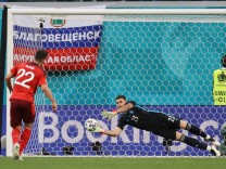 Spain s goalkeeper Unai Simon (R) saves a penalty shot by Switzerland s Fabian Schar in the penalty shootout during the