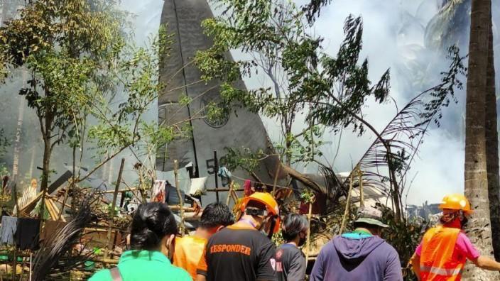 Philippinen: Retter am Wrack des abgestürzten Flugzeugs.